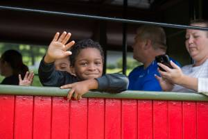 A young boy waving from one the passenger car at Tweetsie Railroad, Blowing Rock, North Carolina.