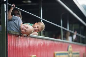 Two brothers sticking their heads out of a passenger car at Tweetsie Railroad.