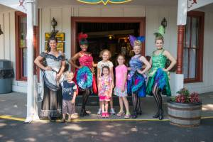 Four can-can girls taking a photo with three young ladies outside of the Palace at Tweetsie Railroad.