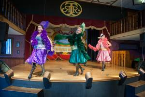 Three can-can girls performing on stage in the Palace at Tweetsie Railroad.