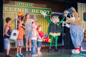 Four young volunteers dancing on stage with Jenny, Hopper and Porter in the Miner's Mountain Theater at Tweetsie Railroad.
