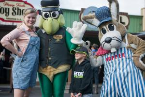 Jenny, Porter and Hopper taking a photo with a small boy on main street at Tweetsie Railroad.