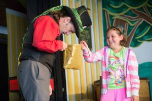 A magician and a young girl performing magic tricks on stage in the Miner's Mountain Theater at Tweetsie Railroad.