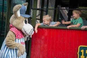 Hopper giving high five to a little boy on a passenger car at Tweetsie Railroad.
