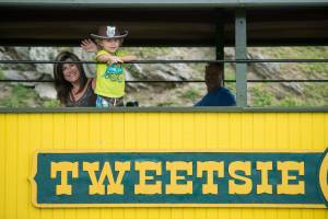 A little boy and his mother waving from a passenger car at Tweetsie Railroad.