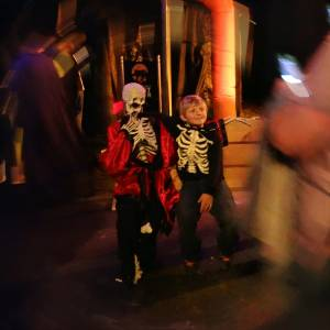 A child sitting with a skeleton prop during Ghost Train Halloween Festival at Tweetsie Railroad, Blowing Rock, North Carolina