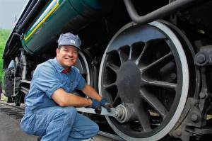 An engineer alongside the wheels of one of the historic coal-powered steam locomotives at Tweetsie Railroad.