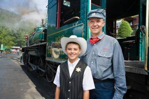 An engineer and young boy with a cowboy hat and sheriff's badge standing in front of historic coal-powered steam locomotive no 190 at Tweetsie Railroad.