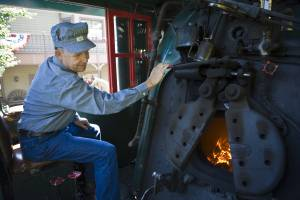 An engineer peaking into the firebox on a historic coal-powered steam locomotive at Tweetsie Railroad.