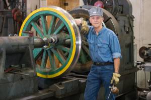An engineer providing maintenance to one of the wheels of the historic coal-powered steam locomotive in the train shop at Tweetsie Railroad.