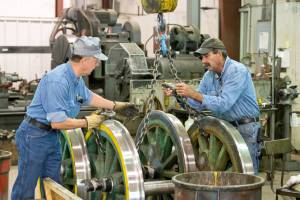 Two engineers working on the wheels of the historic coal-powered steam locomotive in the train shop at Tweetsie Railroad.