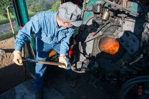 An engineer shoveling coal into the firebox on a historic steam locomotive at Tweetsie Railroad.